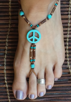 Barefoot sandals designed with turquoise peace symbols surrounded by bamboo, turquoise and wood beads